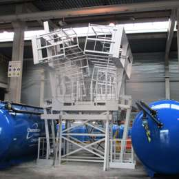 Pivoting industrial platform with counterbalance weights for tank access.